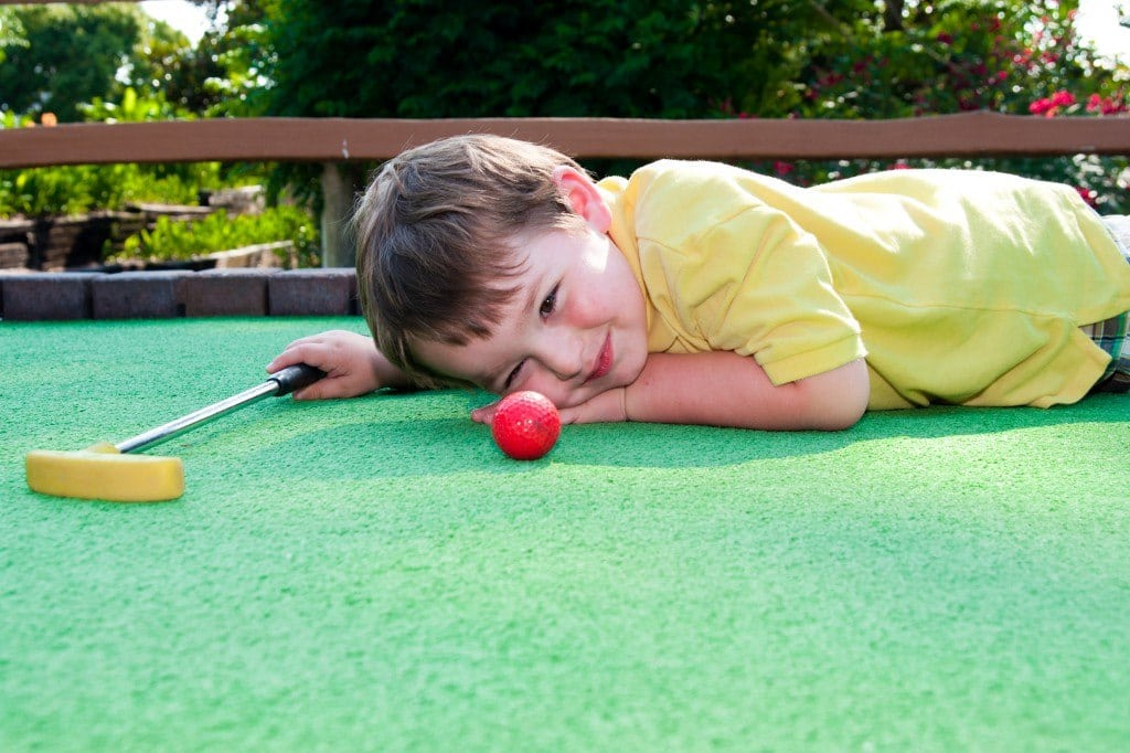 Kid laying on mini golf course