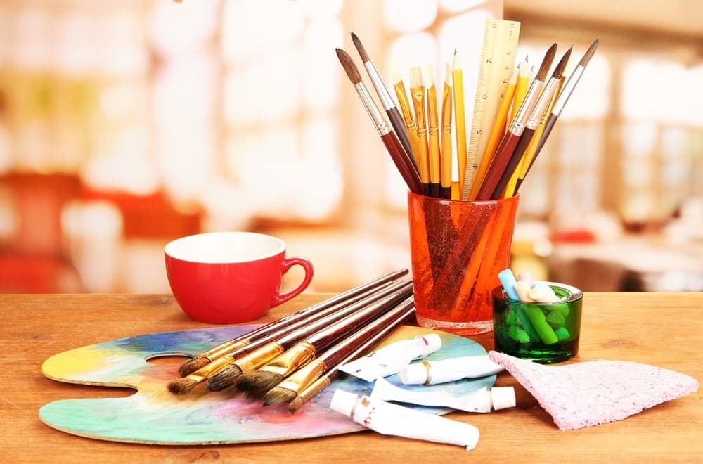 Pencils, brushes, and watercolors on table for arts and crafts