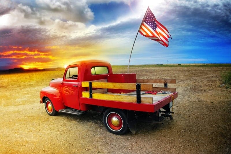 Red pickup truck facing a cloudy sky with the American flag in the back