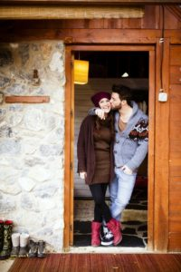 Couple standing in the doorway of a cabin