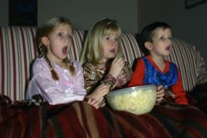 Three kids watching a movie, eating popcorn on the couch while sitting under a red blanket