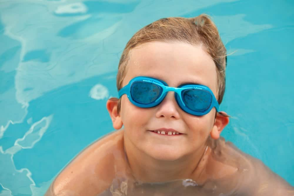 smiling little boy with blue goggles in pool at Smoky Mountain cabin